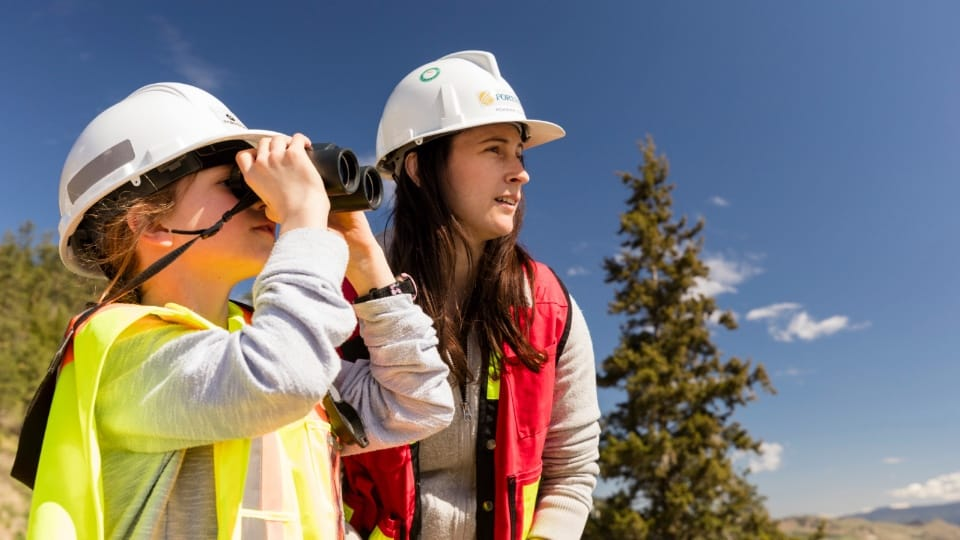 Girl looking through binoculars with FortisBC Hardhat