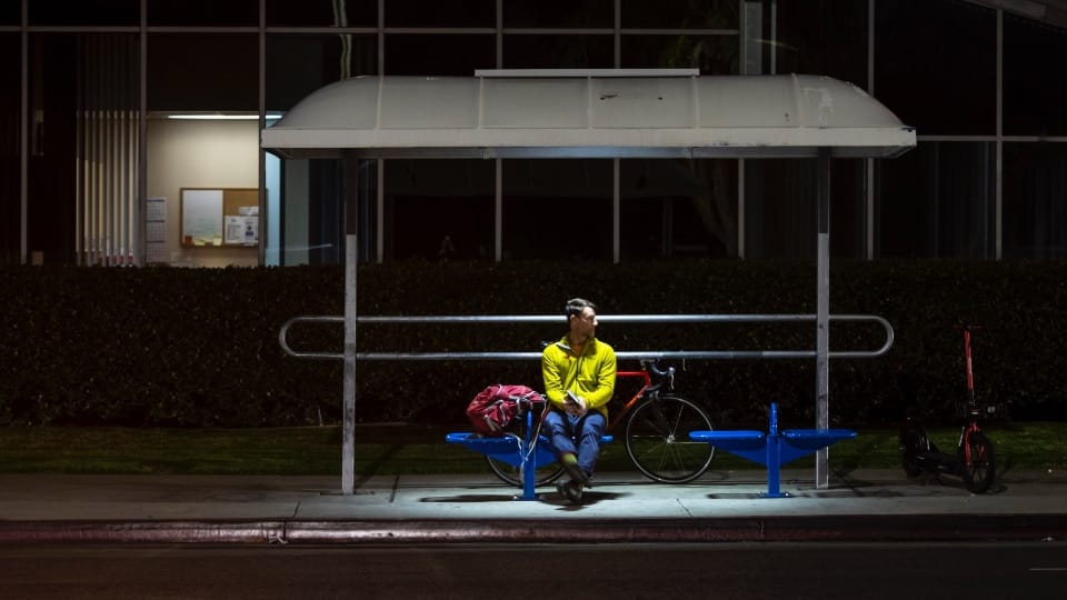 Man at bus stop at night with lights