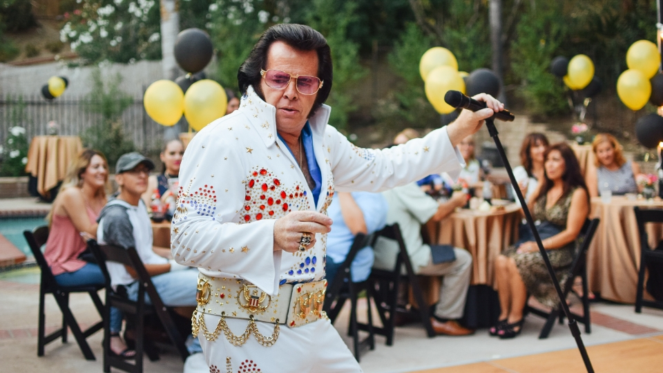 Elvis impersonator in front of a crowd