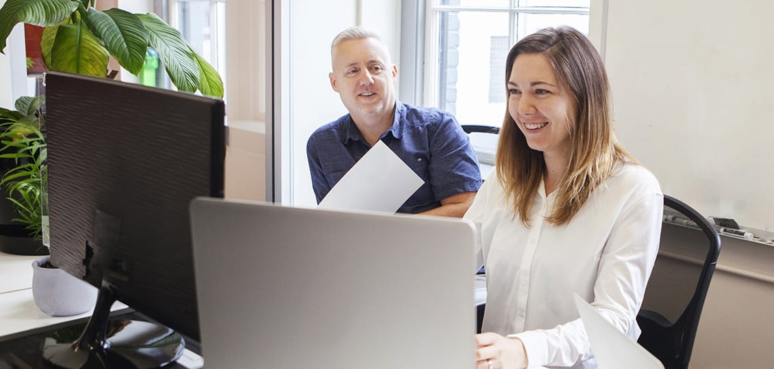 Two people smiling and looking at computer
